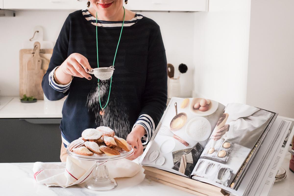 Carlotta e il bassotto che mette lo zucchero a velo su un'alzatine piena di madeleines