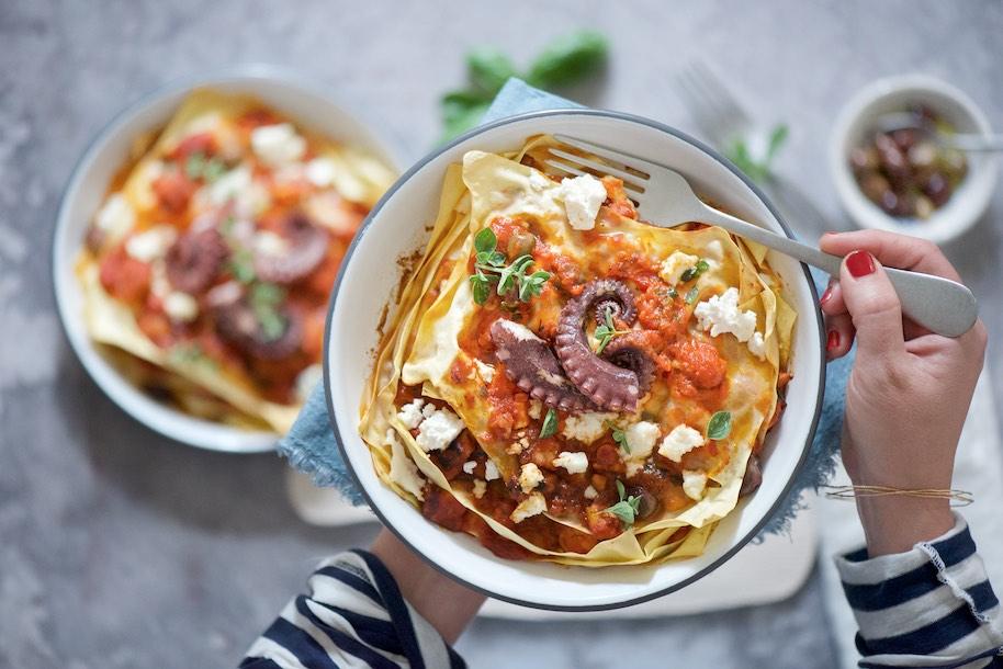 fondina con lasagna con ragù di polpo e mano con forchetta