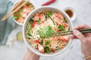 ciotola con noodle di riso,gamberi,foglie di coriandolo e menta, due mani che tengono le bacchette