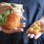 marmellata di prugne mirabelle in un vasetto week tenuto in mano
