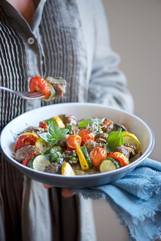 piatto fondo tenuto in mano con polpettone di carne e verdure estive tagliate a rondelle