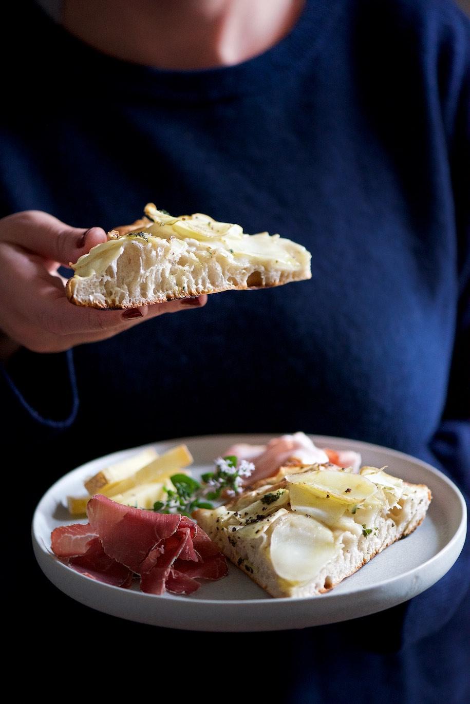 fetta di focaccia con patate tenuta in mano insieme ad un piatto di formaggi e salumi