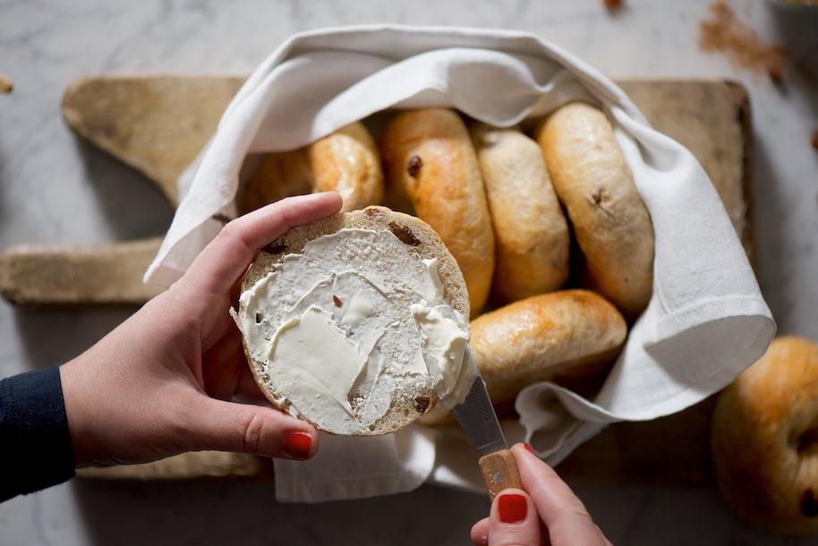 cesta piena di bagels alla cannella e uvetta con mano che sta spalmando di creme cheese un bagel tagliato a metà