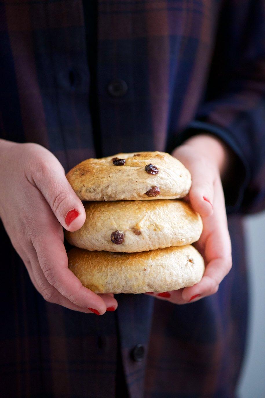 due mani che tengono tre bagels alla cannella e uvetta
