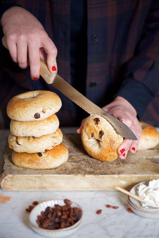 quattro bagels alla cannella e uvetta sovrapposti e una mano che tiene un bagel che viene tagliato a metà