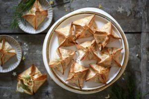 piramidi di pasta fillo ripiene di salmone servite su un piattino dal bordo dorato