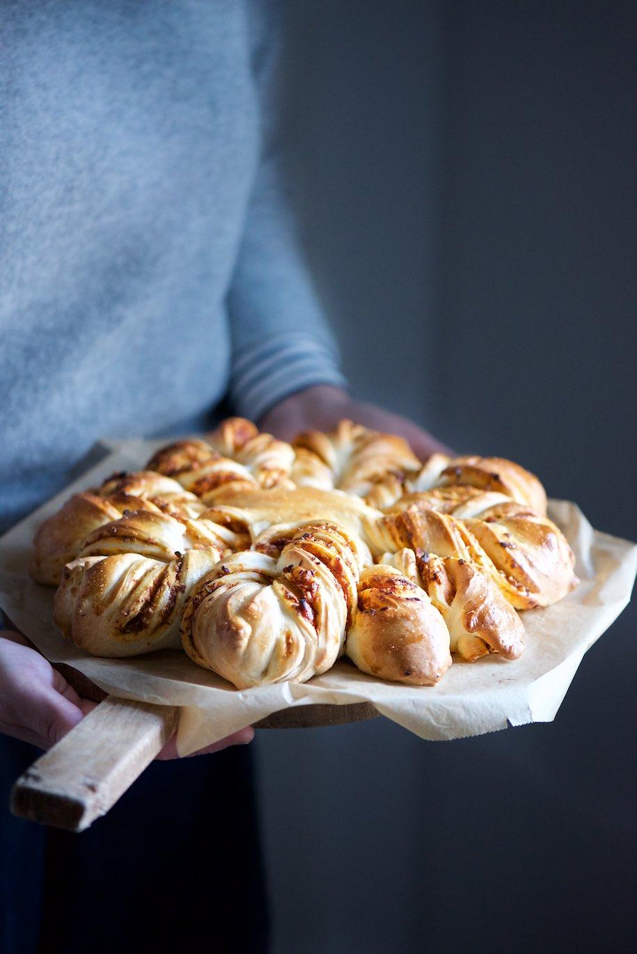 pan briche ripieno di pesto di pomodori secchi appoggiato su un tagliere che viene tenuto in mano