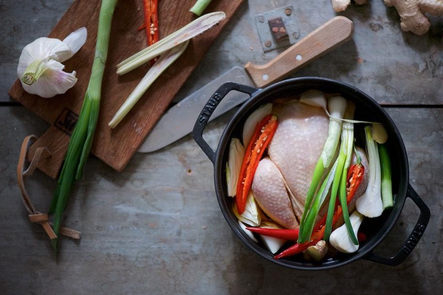 pollo intero in cocotte con peperoncino, cipollotti, zenzero