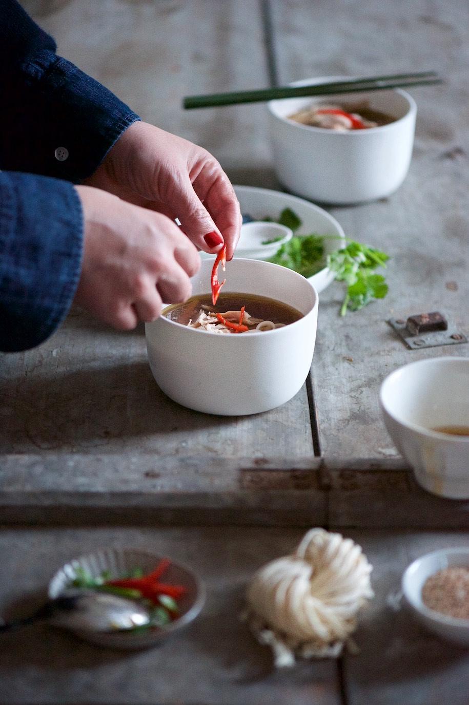 ciotola di noodles, pollo e brodo con due mani che stanno appoggiando del peperoncino
