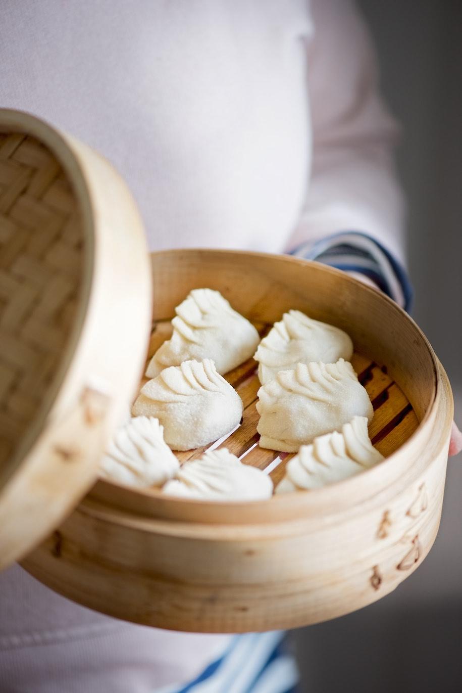 gyoza di maiale in cestino di bambù tenuti in mano