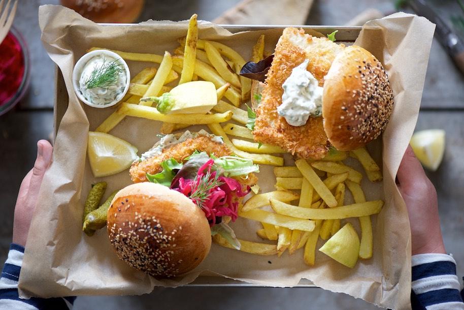 fish burger su vassoio con patatine fritte, spicchi di limone e salsa tartara