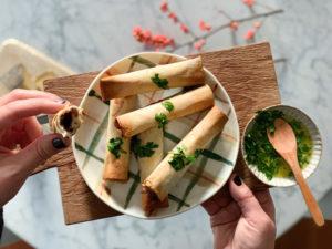 rotolini di pasta fillo con bresaola e formaggio su tagliere di legno